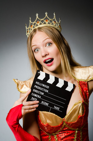 Queen in red dress with movie clapboard photo