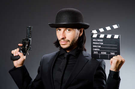 Man with gun and movie clapboard photo