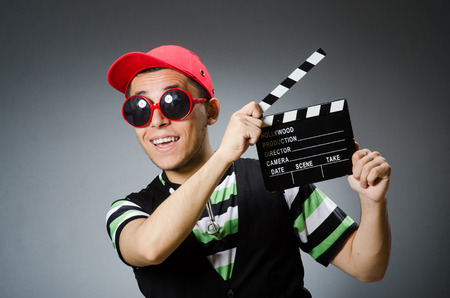 Man with baseball cap and movie board photo