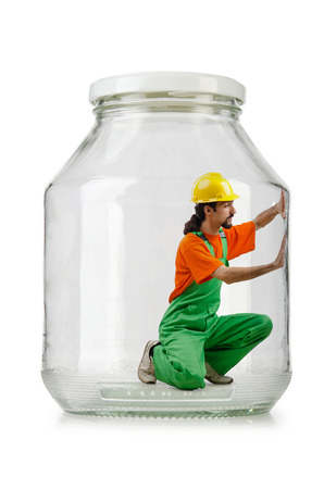 Man in coveralls imprisoned in glass jar Stock Photo