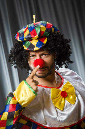 disillusioned: Funny clown in humorous concept against curtain