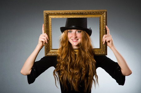 Woman with vintage hat and picture frame photo