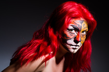 lion face: Woman with tiger face in halloween concept