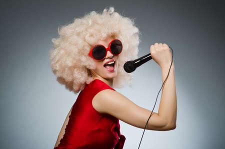 gente cantando: Mujer joven con el micr�fono en el concepto de la m�sica