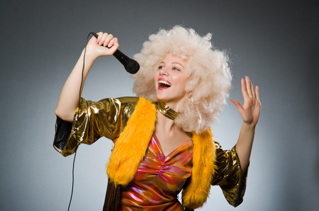 Young woman with mic in music concept Stock Photo