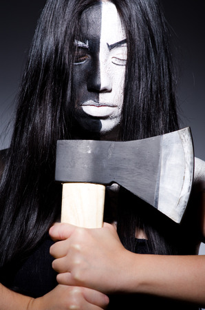 Scary woman with metal axe in halloween concept photo