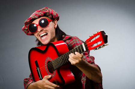 Funny scotsman playing red guitar photo