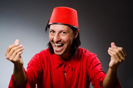 fez: Man in red dress wearing fez hat