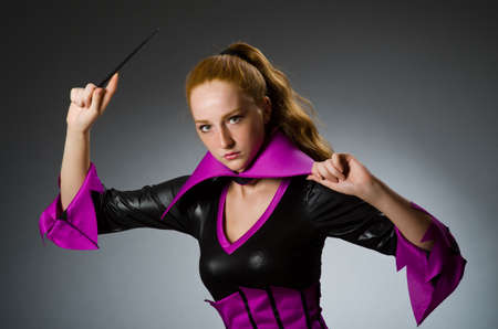 wizardry: Female magician doing tricks on grey background