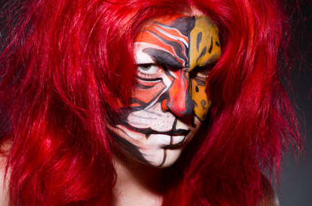 Woman with tiger face in halloween concept photo