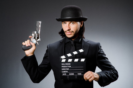 clapboard: Man with gun and movie clapboard