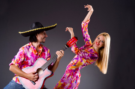 Spanish pair playing guitar and dancing photo