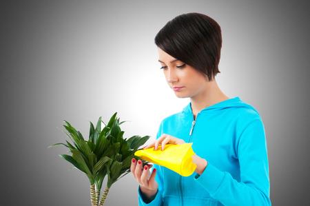 regar las plantas: Joven regar plantas aisladas en blanco