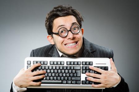 geek: Friki del ordenador con el teclado de la computadora