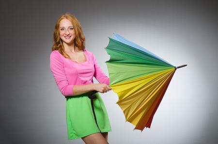 pret a porter: Woman holding colourful umbrella in studio