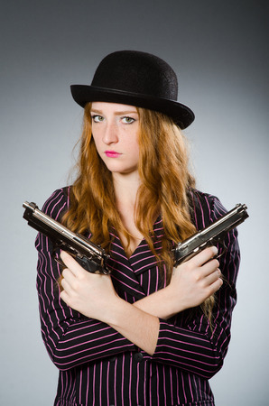 female assassin: Woman gangster with gun in vintage concept