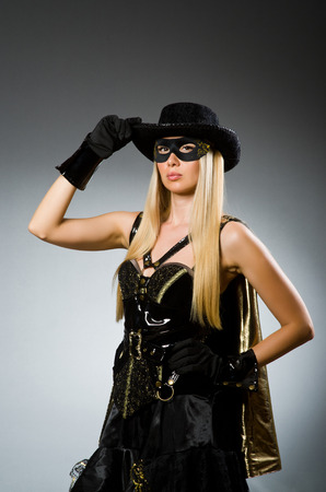 Woman wearing mask against dark background photo