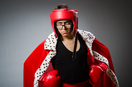 feeble: Funny boxer with red gloves against dark background Stock Photo
