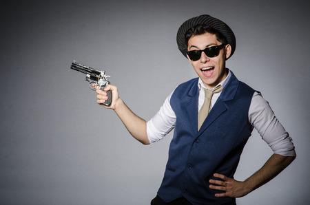 man holding gun: Man wearing sunglasses with gun