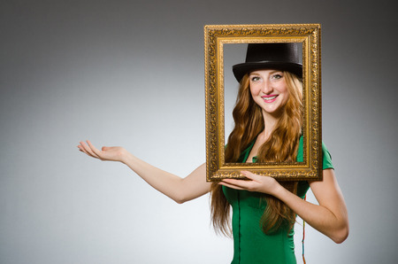 Woman wearing green dress holding picture frame photo
