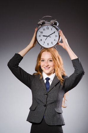 deliverables: Businesswoman with clock being late for her deliverables