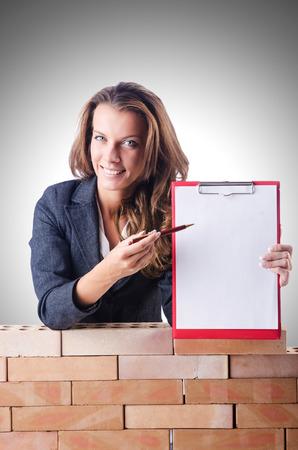 Woman builder and brick wall photo