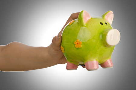 Hand with piggybank on white background photo