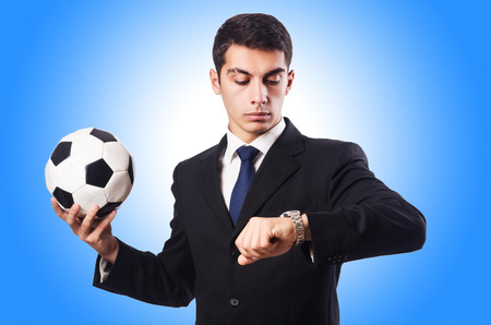 Young businessman with football on white photo