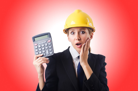 Female construction worker with calculator Stock Photo