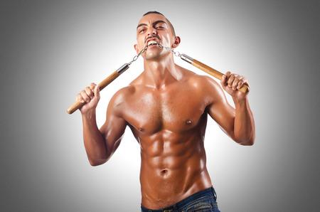 attacker: Man in martial arts concept with nunchucks Stock Photo
