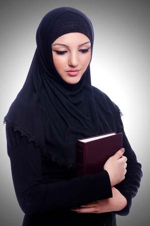 learning  pray: Young muslim woman with book on white
