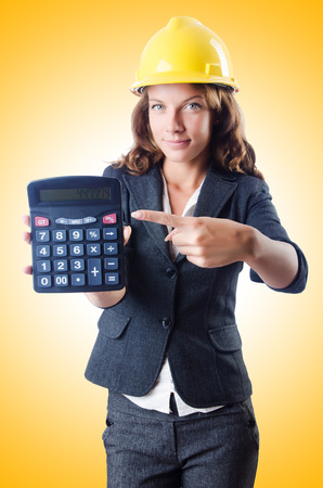 budget repair: Female builder with calculator on white