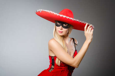 Woman wearing red sombrero and mask Stock Photo