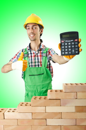 erecting: Expensive construction concept with builder and calculator Stock Photo