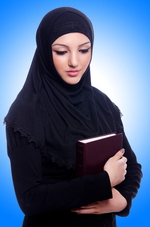 burqa: Young muslim woman with book on white