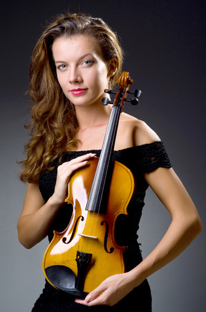 solo violinist: Female musical player against dark background Stock Photo