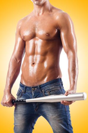 Muscular man with baseball bat on white photo