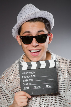 clapperboard: Young camera assistant with clapperboard