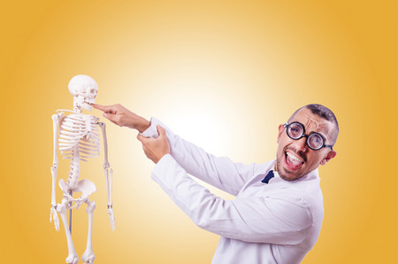 Funny doctor with skeleton isolated on white Stock Photo
