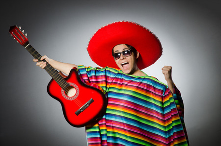 Man in red sombrero playing guitar photo