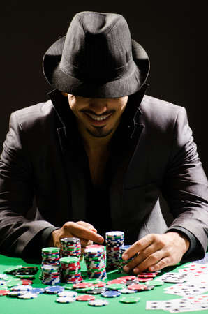 poker chip: Man playing in dark casino