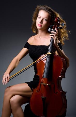 fiddlestick: Female musical player against dark background Stock Photo