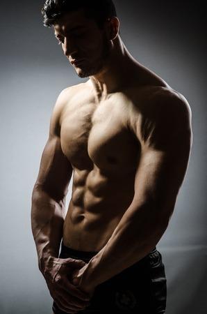 desnudo masculino: Hombre muscular que presenta en el estudio oscuro