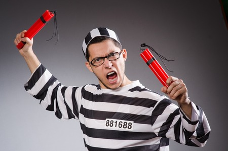 shackled: Funny prisoner with dynamite  isolated on gray Stock Photo