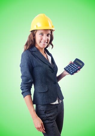 cost estimate: Female builder with calculator against gradient