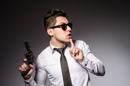 shhh: Young man in cool sunglasses holding gun isolated on gray