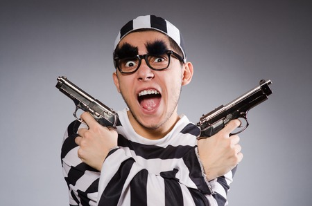 fraudster: Funny prisoner with weapon isolated on gray