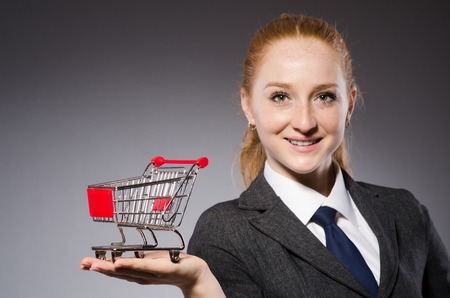 merchandiser: Businesswoman with cart isolated on gray