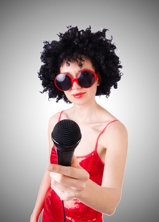 pop star: Pop star with mic in red dress against gradient Stock Photo