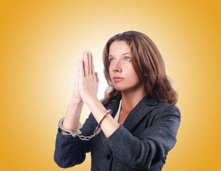 young  cuffs: Female businesswoman with handcuffs against gradient